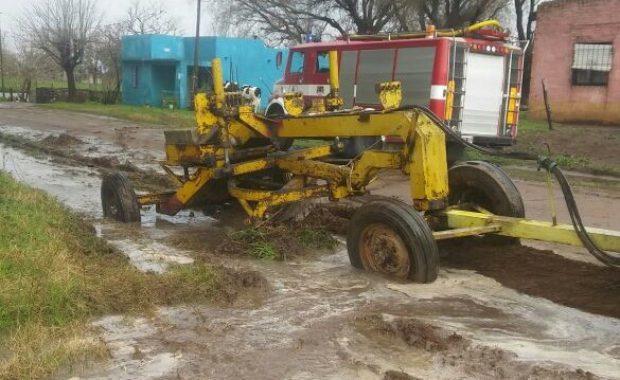 Maquinas municipales y Bomberos Voluntarios trabajando para desagotar calles