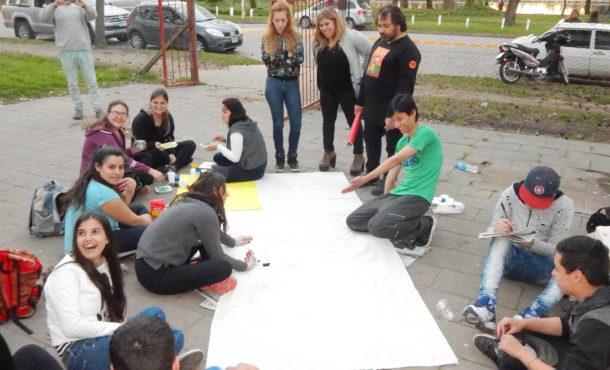 Alumnos trabajando sobre una de las banderas en las 1eras Olimpiadas Juveniles