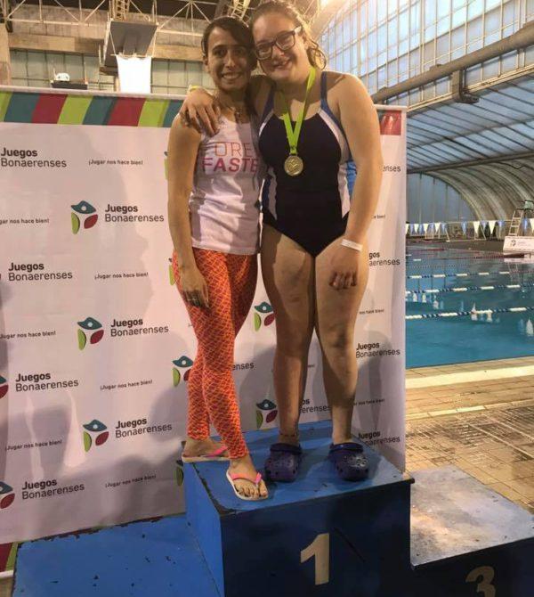 Julia junto a su entrenadora exhbiendo su medalla dorada
