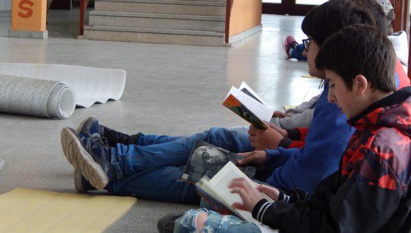 Un grupo de alumnos procede a la lectura de libros tomados de la Biblio Movil