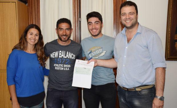 El presidente del Club Ciclistas Unidos de 9 de Julio recibiendo el aporte por parte de Barroso