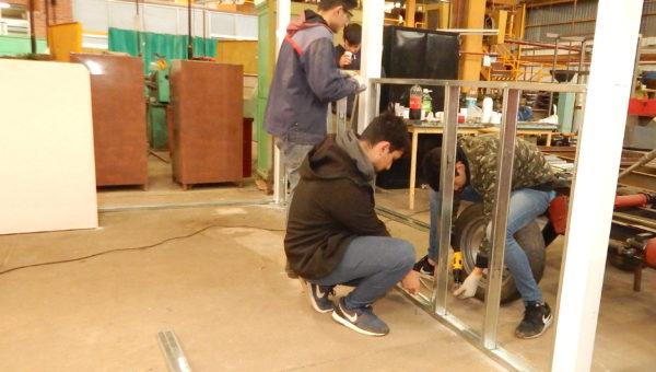 Alumnos que colocan durlok en el Box donde se construira el automovil electrico