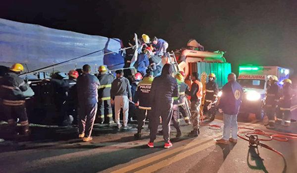 Bomberos al momento de sacar a uno de los choferes que quedo atrapado en la cabina de un de los camiones
