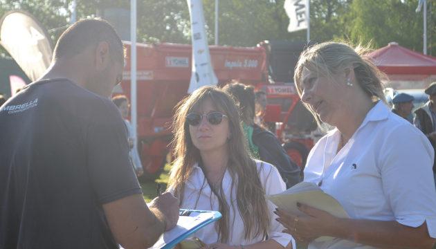 Promotoras de Aca Salud en dialogo con un visitante a la muestra