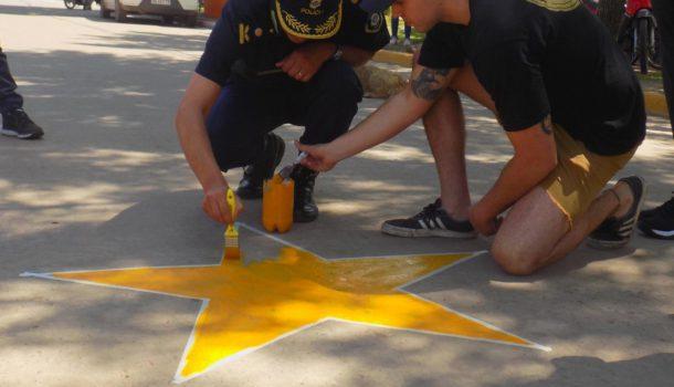 Un efectivo de Policia,Amigos y familiares de Iñaki en Gral Viamonte pintando la primera Estrella Amarilla