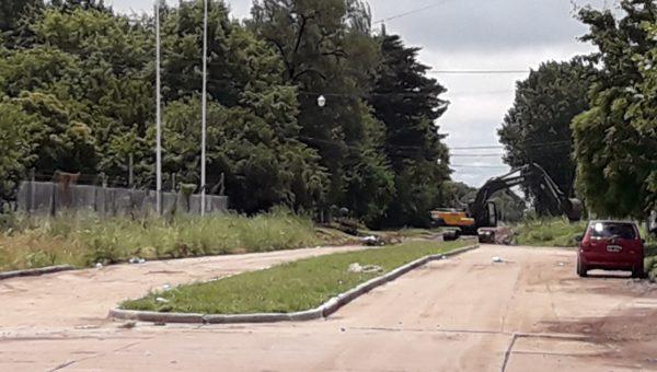 Maquinaria vial municipal trabajando sobre el canal abierto lindante a Av 25 de Mayo limpiando el mismo luego del anegamiento por agua
