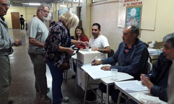 En la media mañana una asociada pasa por la mesa del Distrito Oeste a emitir su voto