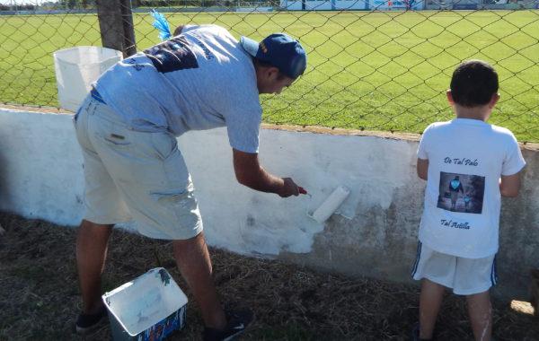 Con el ejemplo, un padre y su hijo trabajan en la pintura del estadio de San Martin