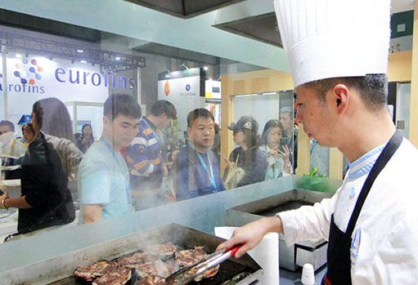 El publico del asia obsevan como se cocina un corte vacuno