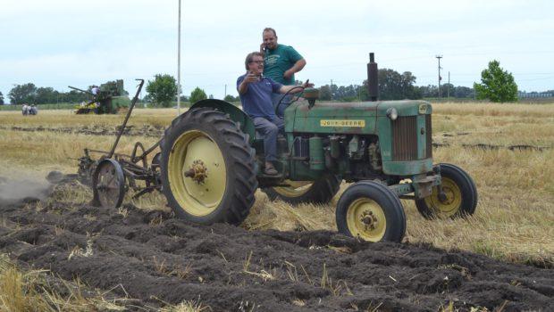 Tractor JD con arado de tres rejas y el disfrute de su conductor