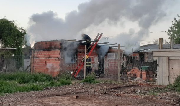 Bomberos trabajando sobre la vivienda damnificada por el fuego
